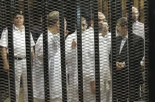 Ousted former Egyptian president Mursi speaks with other senior figures of the Muslim Brotherhood in a cage in a courthouse on the first day of his trial, in Cairo
